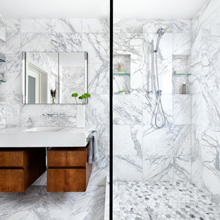 Trendy white tile and marble tile alcove shower photo in Austin with flat-panel cabinets and medium tone wood cabinets