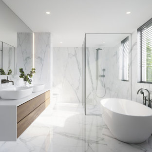 This is an example of a large contemporary master bathroom in New York with flat-panel cabinets, white cabinets, a freestanding tub, a curbless shower, multi-coloured tile, marble, marble floors, tile benchtops, a hinged shower door, yellow benchtops, an enclosed toilet, a double vanity and a floating vanity.