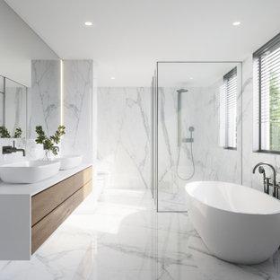 Пример оригинального дизайна: большая главная ванная комната в современном стиле с плоскими фасадами, белыми фасадами, отдельно стоящей ванной, душем без бортиков, разноцветной плиткой, мраморной плиткой, мраморным полом, столешницей из плитки, душем с распашными дверями, желтой столешницей, унитазом, тумбой под две раковины и подвесной тумбой