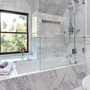 Example of a mid-sized classic master marble tile and white tile marble floor and white floor tub/shower combo design in San Francisco with an undermount tub, a hinged shower door, gray walls and marble countertops