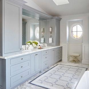 Immagine di una grande stanza da bagno padronale minimal con ante con riquadro incassato, ante grigie, vasca freestanding, piastrelle bianche, piastrelle di marmo, pareti grigie, pavimento in marmo, lavabo sottopiano, top in marmo, pavimento bianco e top bianco