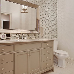 Design ideas for a mid-sized bathroom in New Orleans with a two-piece toilet, mirror tile, white walls, an undermount sink and marble benchtops.