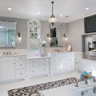 Inspiration for a large timeless master white tile and stone tile marble floor bathroom remodel in Los Angeles with an undermount sink, raised-panel cabinets, white cabinets, marble countertops, an undermount tub, gray walls and a one-piece toilet