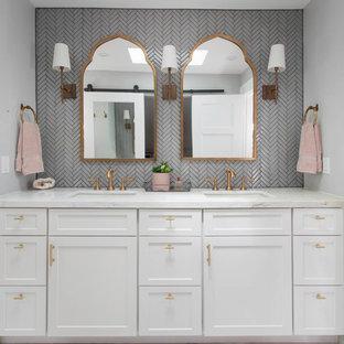 Foto di una stanza da bagno padronale chic di medie dimensioni con ante con riquadro incassato, ante bianche, doccia alcova, WC monopezzo, piastrelle grigie, piastrelle di vetro, pareti grigie, pavimento in marmo, lavabo sottopiano, top in marmo, pavimento bianco, porta doccia a battente e top bianco