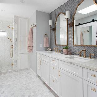 Cette image montre une douche en alcôve principale traditionnelle de taille moyenne avec des portes de placard blanches, un carrelage gris, un carrelage en pâte de verre, un mur gris, un sol en marbre, un lavabo encastré, un plan de toilette en marbre, un sol blanc, un plan de toilette blanc et un placard à porte shaker.