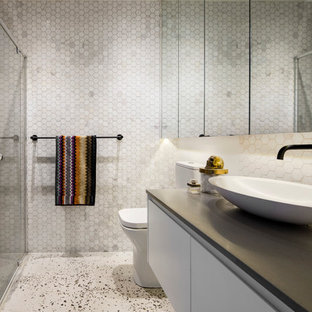 Inspiration for a mid-sized contemporary bathroom in Melbourne with white cabinets, mosaic tile, white walls, concrete floors and marble benchtops.