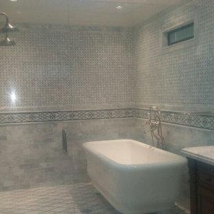 Bild på ett mellanstort vintage en-suite badrum, med luckor med upphöjd panel, skåp i mörkt trä, ett fristående badkar, en dusch i en alkov, grå kakel, kakelplattor, grå väggar, kalkstensgolv, ett undermonterad handfat, marmorbänkskiva, grått golv och dusch med gångjärnsdörr