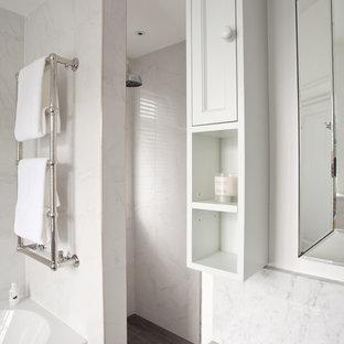 Diseño de cuarto de baño principal, tradicional, de tamaño medio, con armarios estilo shaker, puertas de armario blancas, combinación de ducha y bañera, sanitario de pared, baldosas y/o azulejos grises, baldosas y/o azulejos de mármol, paredes grises, suelo laminado, lavabo integrado, suelo gris, ducha abierta y bañera encastrada