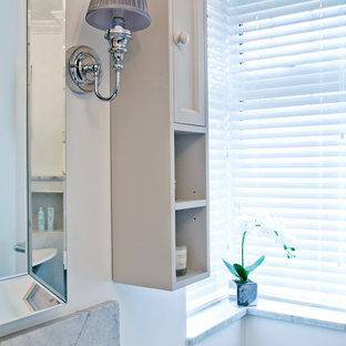 Diseño de cuarto de baño principal, clásico, grande, con armarios con paneles empotrados, puertas de armario grises, bañera exenta, ducha esquinera, sanitario de dos piezas, baldosas y/o azulejos grises, baldosas y/o azulejos de mármol, paredes grises, suelo laminado, lavabo integrado, encimera de mármol, suelo gris y ducha con puerta con bisagras