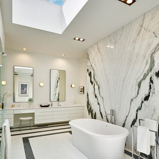 Идея дизайна: огромная главная ванная комната в стиле модернизм с плоскими фасадами, белыми фасадами, отдельно стоящей ванной, душем без бортиков, инсталляцией, черно-белой плиткой, плиткой из листового стекла, белыми стенами, мраморным полом, монолитной раковиной, столешницей из кварцита, белым полом и душем с распашными дверями