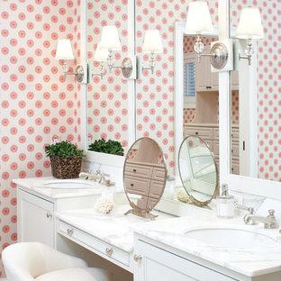 На фото: большая главная ванная комната в морском стиле с мраморной столешницей, врезной раковиной, фасадами с утопленной филенкой, белыми фасадами, отдельно стоящей ванной, угловым душем, каменной плиткой и розовыми стенами с