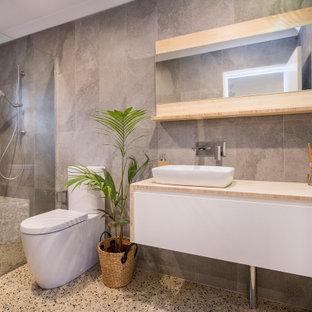 Esempio di una stanza da bagno design di medie dimensioni con pavimento in cemento, doccia aperta, ante lisce, ante bianche, doccia alcova, piastrelle grigie, lavabo a bacinella, top in legno, pavimento grigio e top beige