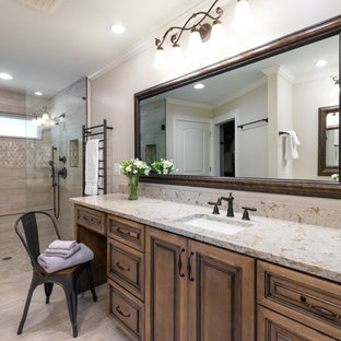Example of a classic gray tile gray floor walk-in shower design in Atlanta with raised-panel cabinets, medium tone wood cabinets, gray walls, an undermount sink, a hinged shower door and beige countertops