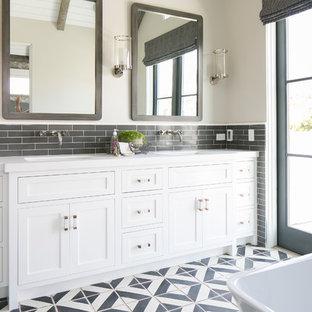 Exemple d'une salle de bain bord de mer avec un lavabo encastré, un placard à porte shaker, des portes de placard blanches, une baignoire indépendante, un carrelage gris, un mur blanc et un sol multicolore.
