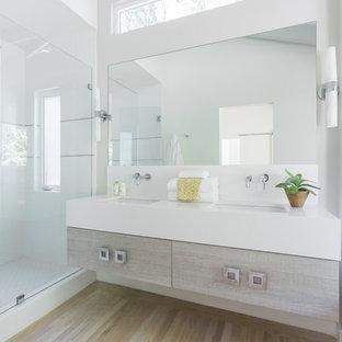 サンフランシスコの広いビーチスタイルのおしゃれな浴室 (フラットパネル扉のキャビネット、ヴィンテージ仕上げキャビネット、置き型浴槽、オープン型シャワー、白いタイル、セラミックタイル、白い壁、淡色無垢フローリング、アンダーカウンター洗面器、珪岩の洗面台、マルチカラーの床、オープンシャワー、白い洗面カウンター) の写真
