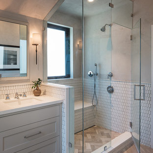Corner shower - transitional master white tile beige floor corner shower idea in San Francisco with shaker cabinets, gray cabinets, beige walls, an undermount sink and a hinged shower door