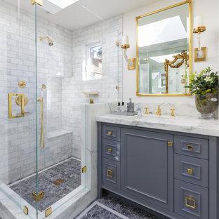 Foto de cuarto de baño clásico, de tamaño medio, con puertas de armario grises, ducha esquinera, baldosas y/o azulejos blancos, baldosas y/o azulejos de mármol, paredes blancas, suelo con mosaicos de baldosas, lavabo bajoencimera, suelo gris, ducha con puerta con bisagras y armarios tipo mueble