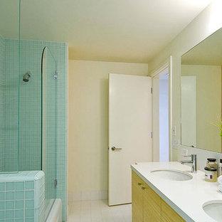 Imagen de cuarto de baño principal, contemporáneo, con lavabo bajoencimera, armarios con paneles lisos, puertas de armario de madera clara, encimera de vidrio reciclado, bañera encastrada, baldosas y/o azulejos azules, baldosas y/o azulejos de vidrio, paredes blancas y suelo de baldosas de porcelana