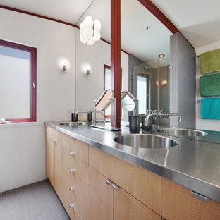 Eklektisk inredning av ett mellanstort grå grått en-suite badrum, med släta luckor, skåp i ljust trä, en dusch i en alkov, en toalettstol med hel cisternkåpa, grå kakel, keramikplattor, vita väggar, klinkergolv i keramik, ett integrerad handfat, bänkskiva i rostfritt stål, grått golv och dusch med gångjärnsdörr