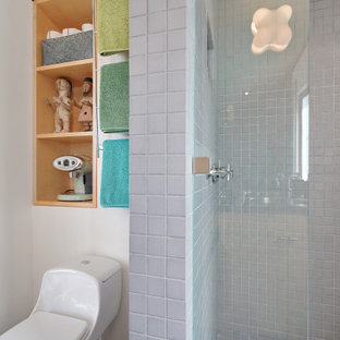 Mid-sized eclectic master gray tile and ceramic tile ceramic floor and gray floor alcove shower photo in San Francisco with flat-panel cabinets, light wood cabinets, a one-piece toilet, white walls, an integrated sink, stainless steel countertops, a hinged shower door and gray countertops
