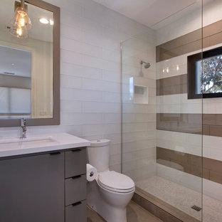 Immagine di una stanza da bagno con doccia minimal di medie dimensioni con ante lisce, ante beige, doccia alcova, WC monopezzo, piastrelle bianche, piastrelle di vetro, pareti bianche, pavimento con piastrelle in ceramica, lavabo sottopiano e top in quarzo composito