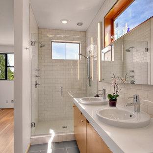 Modernes Badezimmer mit Einbauwaschbecken, flächenbündigen Schrankfronten, hellbraunen Holzschränken, Duschnische, weißen Fliesen, Metrofliesen und grauem Boden in Seattle
