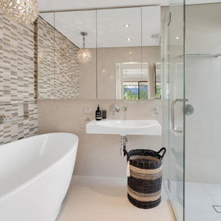 Photo of a mid-sized contemporary master bathroom in Gold Coast - Tweed with a drop-in tub, a corner shower, beige tile, gray tile, porcelain tile, porcelain floors, a wall-mount sink, beige floor, a hinged shower door, a niche and a single vanity.