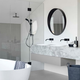 Inspiration for a large contemporary master bathroom in Sydney with flat-panel cabinets, grey cabinets, a freestanding tub, a double shower, a one-piece toilet, white tile, ceramic tile, white walls, ceramic floors, a drop-in sink, marble benchtops, grey floor, a hinged shower door and grey benchtops.