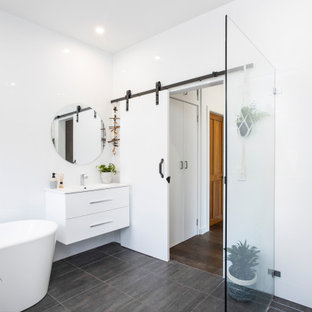 This is an example of a mid-sized contemporary master bathroom in Sydney with furniture-like cabinets, white cabinets, a freestanding tub, an open shower, white tile, ceramic tile, white walls, ceramic floors, an integrated sink, solid surface benchtops, grey floor, an open shower and white benchtops.