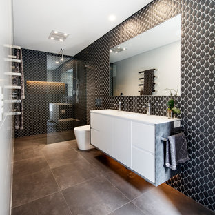 Expansive contemporary 3/4 bathroom in Sydney with flat-panel cabinets, white cabinets, a curbless shower, a one-piece toilet, black tile, an integrated sink, brown floor, an open shower, white benchtops, porcelain tile, brown walls, porcelain floors and solid surface benchtops.