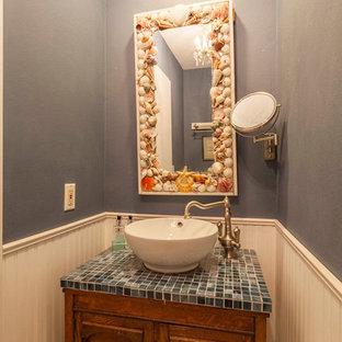Immagine di una piccola stanza da bagno costiera con consolle stile comò, ante in legno bruno, WC monopezzo, piastrelle blu, lastra di vetro, pareti blu, pavimento con piastrelle in ceramica, lavabo a bacinella e top in vetro