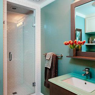 Diseño de cuarto de baño tradicional renovado con armarios con paneles lisos, puertas de armario de madera en tonos medios, encimera de vidrio, ducha empotrada, baldosas y/o azulejos blancos, baldosas y/o azulejos de cemento y paredes azules