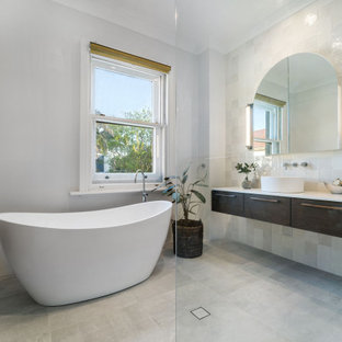 Design ideas for a large contemporary 3/4 bathroom in Sydney with furniture-like cabinets, brown cabinets, a freestanding tub, an open shower, a one-piece toilet, multi-coloured tile, ceramic tile, grey walls, ceramic floors, granite benchtops, multi-coloured floor, an open shower, white benchtops, a single vanity and a floating vanity.