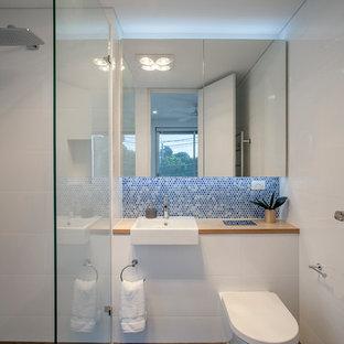 Ispirazione per una stanza da bagno con doccia design con doccia a filo pavimento, WC sospeso, pareti bianche, lavabo da incasso, top in legno, pavimento nero, doccia aperta e top marrone