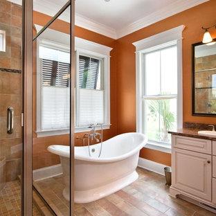 Cette image montre une salle de bain traditionnelle avec une baignoire indépendante, un plan de toilette en granite et un mur orange.