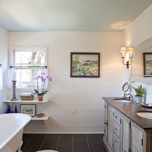 Example of a mid-sized country master white tile and subway tile ceramic floor and black floor bathroom design in Atlanta with an undermount sink, louvered cabinets, medium tone wood cabinets, soapstone countertops, white walls and a hinged shower door