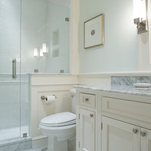 Alcove shower - small traditional 3/4 white tile and subway tile marble floor and gray floor alcove shower idea in Charleston with blue walls, recessed-panel cabinets, white cabinets, a two-piece toilet, an undermount sink, marble countertops, gray countertops and a hinged shower door