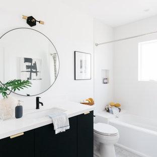 Esempio di una grande stanza da bagno con doccia country con ante lisce, ante nere, vasca ad alcova, vasca/doccia, WC a due pezzi, pareti bianche, pavimento in gres porcellanato, lavabo sottopiano, pavimento grigio, top bianco, nicchia, mobile bagno incassato e un lavabo
