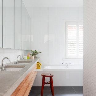 Modelo de cuarto de baño actual, de tamaño medio, con lavabo bajoencimera, armarios con paneles lisos, puertas de armario de madera oscura, encimera de cemento, bañera encastrada, ducha empotrada, baldosas y/o azulejos blancos, baldosas y/o azulejos de cerámica, paredes blancas y suelo de baldosas de porcelana