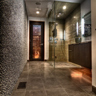 Example of a large 1960s master gray tile and pebble tile black floor corner shower design in Los Angeles with flat-panel cabinets, dark wood cabinets, beige walls and a hinged shower door