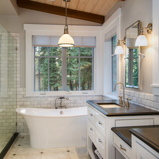 Bathroom - large rustic master white tile and subway tile marble floor bathroom idea in San Francisco with an undermount sink, beaded inset cabinets, white cabinets, soapstone countertops and gray walls