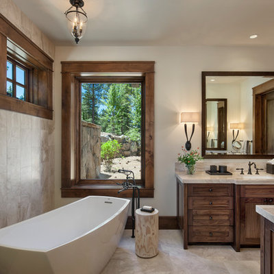 Inspiration for a large rustic master beige tile and travertine tile beige floor freestanding bathtub remodel in Sacramento with an undermount sink, marble countertops, shaker cabinets, dark wood cabinets and beige walls