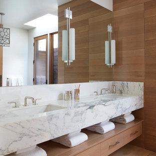 Modelo de cuarto de baño principal, contemporáneo, de tamaño medio, con armarios con paneles lisos, puertas de armario de madera oscura, paredes marrones, suelo de madera en tonos medios, lavabo bajoencimera, encimera de mármol y suelo marrón