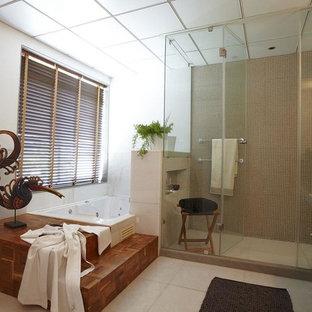 Esempio di una grande stanza da bagno padronale industriale con ante di vetro, vasca idromassaggio, piastrelle bianche e pareti bianche