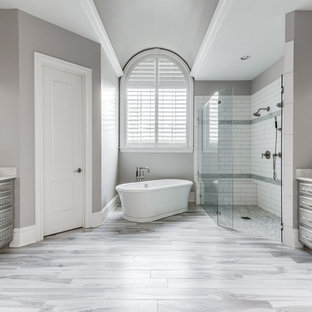 Inspiration for a large transitional master gray tile and terra-cotta tile porcelain floor and gray floor bathroom remodel in Charlotte with gray cabinets, gray walls, an undermount sink, engineered quartz countertops, a hinged shower door and gray countertops