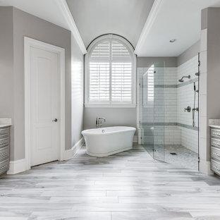 Modelo de cuarto de baño principal, clásico renovado, grande, con puertas de armario grises, bañera exenta, ducha a ras de suelo, baldosas y/o azulejos grises, baldosas y/o azulejos de terracota, paredes grises, suelo de baldosas de porcelana, lavabo bajoencimera, encimera de cuarzo compacto, suelo gris, ducha con puerta con bisagras y encimeras grises