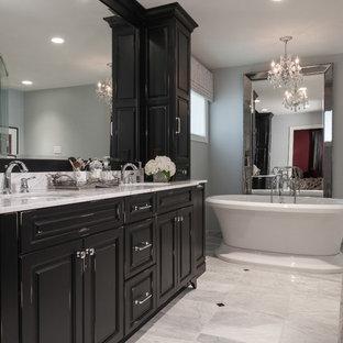 Inredning av ett klassiskt mellanstort en-suite badrum, med ett undermonterad handfat, luckor med upphöjd panel, svarta skåp, marmorbänkskiva, ett fristående badkar, grå väggar och marmorgolv