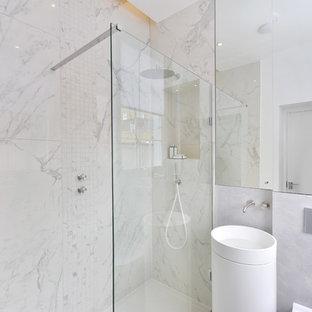 Modelo de cuarto de baño con ducha, actual, pequeño, con armarios tipo vitrina, ducha abierta, sanitario de una pieza, baldosas y/o azulejos grises, baldosas y/o azulejos de piedra, paredes blancas, lavabo con pedestal y encimera de mármol