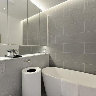 Ejemplo de cuarto de baño contemporáneo, pequeño, con armarios tipo vitrina, bañera exenta, ducha abierta, sanitario de una pieza, baldosas y/o azulejos grises, baldosas y/o azulejos de piedra, paredes grises, lavabo con pedestal y encimera de mármol