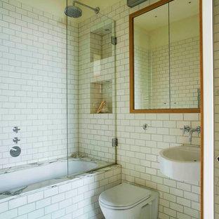 Modelo de cuarto de baño principal, ecléctico, pequeño, con puertas de armario blancas, bañera encastrada, combinación de ducha y bañera, sanitario de pared, baldosas y/o azulejos blancos, baldosas y/o azulejos de porcelana, paredes blancas, suelo de mármol, lavabo suspendido, suelo gris y ducha con puerta con bisagras